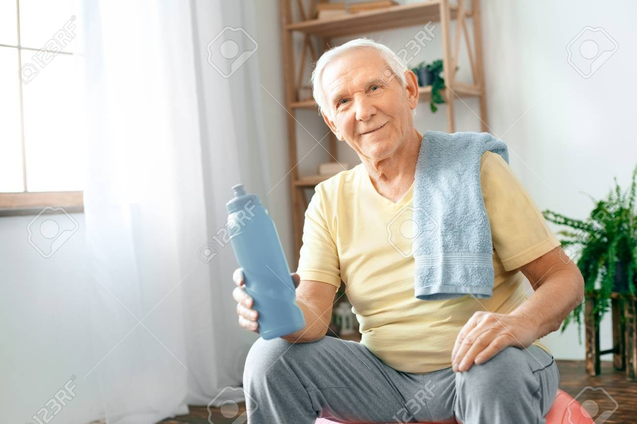94717876-senior-man-exercise-at-home-sitting-on-exercise-ball-rest-drinking-water.jpg